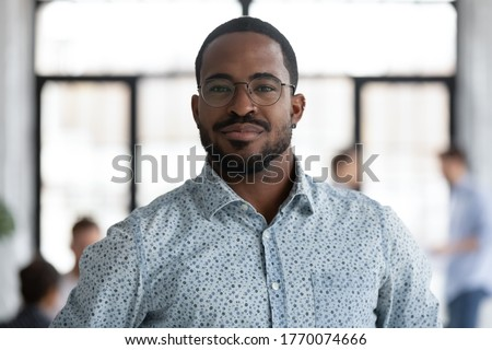 Head shot of african self-assured executive manager portrait, successful staff member company employee pose for camera photo shooting standing in office. Firm owner, proud founder, leadership concept