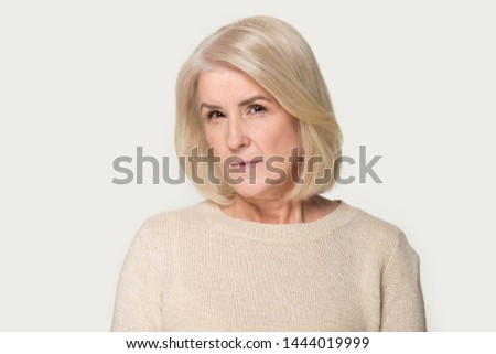 Head shot of angry old woman looking at camera. Suspicious elderly woman showing distrustful look at studio isolated on gray background. Mistrustful, confused, shy, trustless, scared, evil person