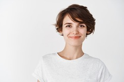 Head shot of beautiful caucasian woman with short haircut, smiling and looking confident, standing in t-shirt on white background.