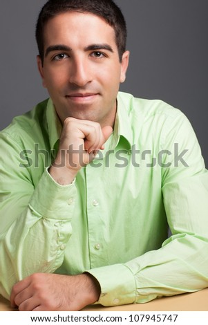 Head shot of handsome young adult man wearing a green shirt looking at camera on solid studio grey background.