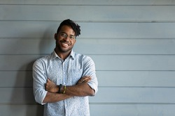 Head shot of handsome young African American guy, young Black man with dreads wearing casual stylish shirt, glasses, keeping hands folded, smiling at camera. Male portrait with copy space