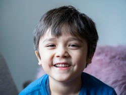 Head shot of healthy kid, Portrait happy child looking at camera with smiling face, candid shot cute little boy relaxing stay at home during covid lock down.Positive children concept,Social distancing
