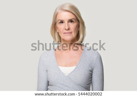 Head shot of serious old aged woman looking at camera. Elderly female portrait, person in years. Successful businesswoman, ceo, director, manager, banker, hr. Studio photo isolated on grey background