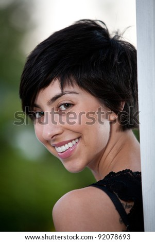 Head shot of young girl peeking out from behind a post in color