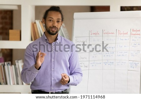 Head shot portrait African American man teacher recording webinar, explaining, speaking and looking at camera, mentor coach leading online lesson, making flip chart presentation, remote education