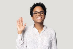 Head shot portrait african pretty young woman in glasses smiles looks at camera raise palm wave hand makes gesture of greeting friendly attitude good relation posing isolated on grey studio background