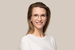 Head shot portrait attractive happy smiling woman in glasses looking at camera, beautiful female in white t-shirt, satisfied student, confident businesswoman, isolated on grey studio background