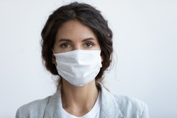 Head shot portrait attractive woman looking at camera wear medical or surgical blue colour face mask protecting from COVID19 or corona virus. Personal care during pandemic infectious disease outbreak