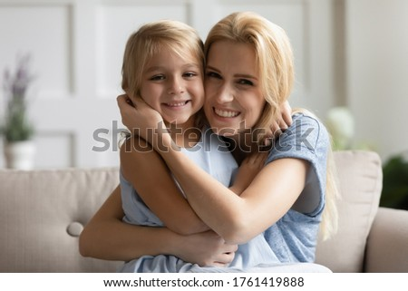 Head shot portrait beautiful mother cuddles lovely little daughter family sitting on sofa smile look at camera spend time together enjoy games playing having fun relish funny activity at home concept