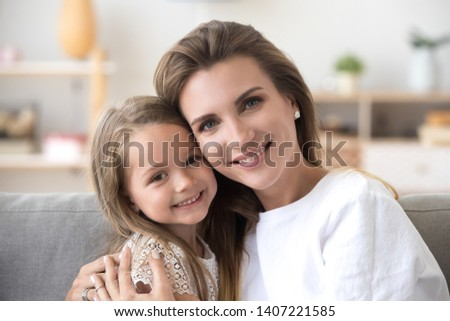 Head shot portrait beautiful young mother embrace little daughter supporting and caring sitting in living room at home spend time together. Happy motherhood or custody new mum for adopted kid concept