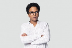 Head shot portrait close up annoyed African American woman in glasses rolling eyes, disappointed girl with arms crossed irritated by boring routine worker bad news, isolated on grey background