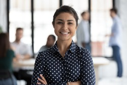Head shot portrait close up smiling confident beautiful Indian businesswoman standing in modern office room with arms crossed, successful executive team leader mentor posing for corporate photo