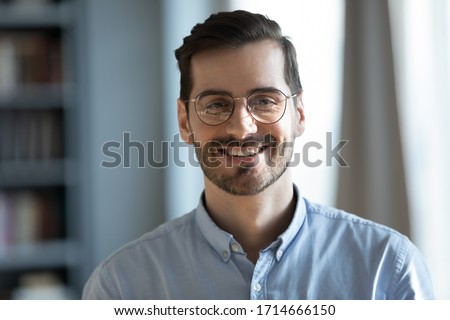 Head shot portrait close up smiling confident businessman wearing glasses looking at camera, standing in modern cabinet, successful happy young man, employee, worker in eyewear posing for photo