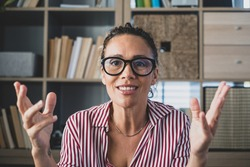 Head shot portrait confident businesswoman coach wearing glasses looking at camera and talking, mentor speaker holding online lesson, explaining, sitting at wooden work desk in modern cabinet