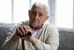 Head shot portrait depressed lonely elderly man with wooden cane looking at camera, frustrated mature male folded hands on walking stick, sitting on couch alone, loneliness and solitude