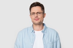 Head shot portrait dissatisfied man in eyeglasses frowning eyebrows having dissatisfied grumpy face expression posing over grey white studio background negative emotions irritated person concept image