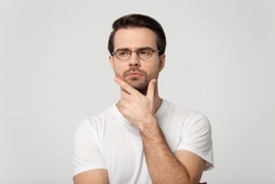 Head shot portrait european appearance serious thoughtful man wear glasses white t-shirt looking away touch chin posture of indecision and doubting feelings, thinker isolated on gray studio background
