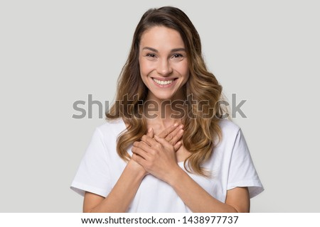 Head shot portrait grateful hopeful young woman holding hands on chest, pleased young female looking at camera, feeling love, gratitude, appreciation, thanking fate, isolated on studio background