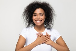 Head shot portrait happy african woman in white t-shirt pose grey background smiling looking at camera holding hands on chest feels gratitude, gesture of sincere feelings from heart and love concept