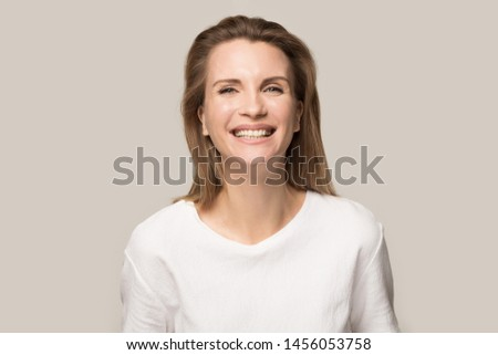 Head shot portrait happy cheerful attractive woman laughing, looking at camera, funny female with healthy wide white smile having fun, satisfied client customer, isolated on grey studio background