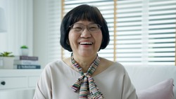 Head shot portrait happy healthy middle aged asian woman with eyeglasses sitting on sofa at home. Old lady laughing, smiling and looking at video camera in living room. Screen video call shot.