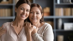 Head shot portrait happy two generations of women hugging, standing at home, smiling mature elderly mother embracing beautiful grownup daughter from back, family posing for photo together