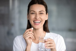 Head shot portrait happy woman holds pill glass of water looks at camera, takes daily medicine vitamin D, omega 3 supplements, skin hair nail strengthen and beauty, medication for health care concept