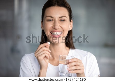 Head shot portrait happy woman holds pill glass of water looks at camera, takes daily medicine vitamin D, omega 3 supplements, skin hair nail strengthen and beauty, medication for health care concept Foto stock ©