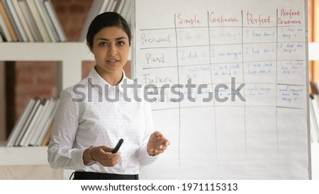 Head shot portrait Indian woman teacher making flip chart presentation, recording webinar, speaking and looking at camera, mentor coach leading online lesson, teaching and explaining, e-learning