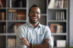 Head shot portrait laughing excited African American man wearing glasses standing with arms crossed in modern cabinet, positive young male confident businessman in eyewear looking at camera