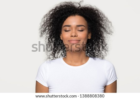 Head shot portrait mixed race attractive calm woman in white t-shirt isolated on grey background, closed eyes smile enjoy fresh air dreaming about future feels satisfied and tranquil conceptual image