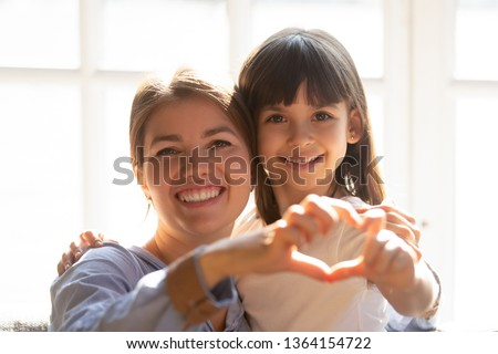 Head shot portrait mother and daughter make heart shape with hands fingers hugging sitting on couch sunlight through the window. Adoption and custody, health medical pediatric insurance, love concept