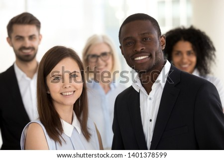 Head shot portrait of excited diverse employees standing in office, posing for photo, looking at camera, smiling African American leader and female manager with office workers team, teamwork concept