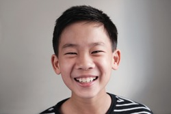 Head shot portrait of happy, confident and healthy mixed race Asian preteen teenage boy face, smiling