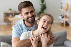 Head shot portrait of happy excited young couple in love at home, handsome smiling husband embracing, holding in hands attractive laughing wife, looking at camera, having fun together in living room