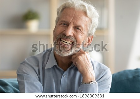 Head shot portrait of happy middle aged older retired man laughing at funny joke. Emotional smiling elderly grandfather looking at camera, enjoying video call or distant communicating with friends.