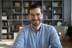 Head shot portrait of happy young handsome confident man in eyeglasses, looking at camera sitting at table at home office. Smiling pleasant businessman holding video call conversation at workplace.