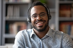 Head shot portrait of smiling African American male call center agent in glasses wireless headset, happy positive biracial man telemarketer in spectacles and headphones look at camera posing in office