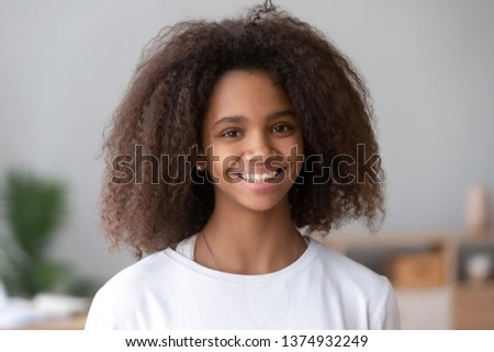 Head shot portrait of smiling African American teenage girl, feeling happy, posing for photo at home, beautiful positive mixed race teenager looking at camera, laughing, having fun
