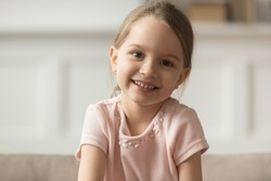 Head shot portrait of smiling little girl looking at camera, preschool child playing with camera, recording vlog or making video call, communicating online, using webcam, sitting on couch at home