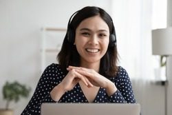 Head shot portrait of smiling millennial asian ethnicity female employee wearing modern headset with microphone, working remotely from home, communicating with colleagues by video call application.