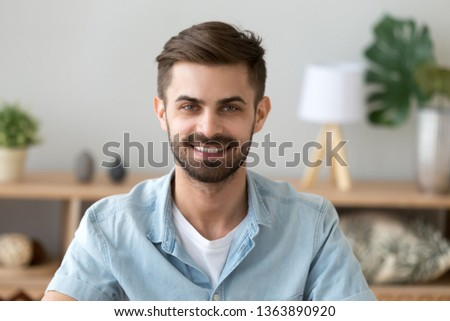 Photo of Head shot portrait of smiling satisfied man looking at camera, sitting at home or work, posing for picture indoors, happy satisfied businessman, confident guy making photo in office