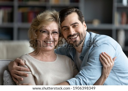 Head shot portrait of smiling young caucasian man embracing affectionate older senior mother in glasses, enjoying sweet tender time indoor, spending weekend leisure together, family relations concept.