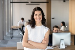 Head shot portrait of successful smiling businesswoman with arms crossed standing in office, looking at camera, happy female employee, team leader posing for company photo, beautiful woman at work