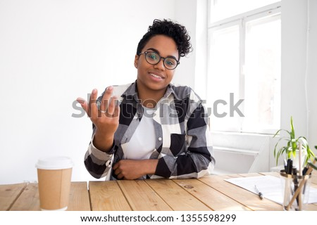 Head shot portrait of talking smiling African American woman wearing glasses, looking at camera, making video call, chatting with friends, blogger recording video, sharing thoughts, sitting at desk