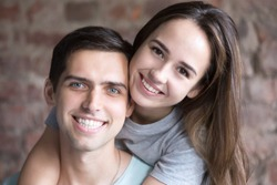 Head shot portrait of young couple in love, smiling people. Happy husband and wife. Friendship. Look at camera. Close up.