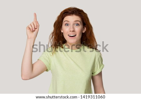 Head shot portrait red-headed woman point finger up find answer to question on grey studio background, funny girl gesturing with hand feels excited with good idea inspiration motivation eureka concept
