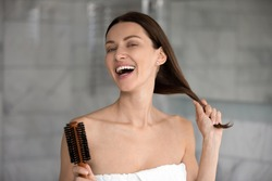 Head shot portrait 35s cheerful woman after take a bath holds hairbrush tidy her strong healthy hair, morning beauty routine lifestyle, treatment for perfect hair growth advertising, haircare concept