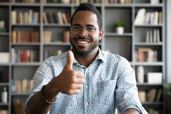 Head shot portrait satisfied smiling African American man wearing glasses showing thumb up, excited businessman student looking at camera, positive customer recommending service, good quality