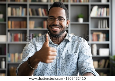 Head shot portrait satisfied smiling African American man wearing glasses showing thumb up, excited businessman student looking at camera, positive customer recommending service, good quality Foto d'archivio ©